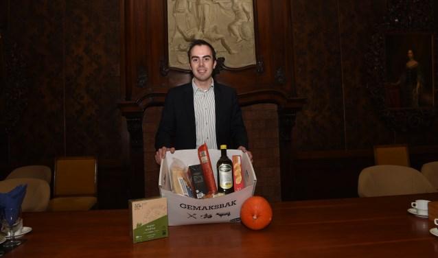 """Wethouder Mike van der Geld heeft van de Sligro in Den Bosch alvast een pakket met levensmiddelen gekregen voor de Voedselbank. """"Die kan wel een steuntje in de rug gebruiken."""""""