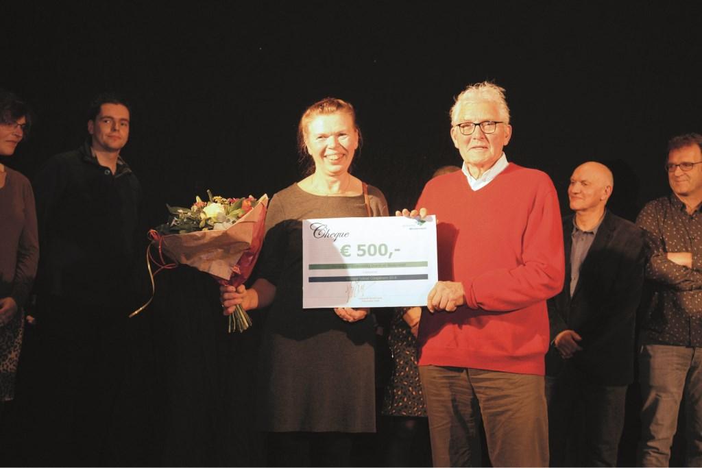 De bestuursleden Piet van Schaik en Hillie van Mourik van de Stichting Kerstontmoeting Duiven en Westervoort met de cheque van 500 euro.