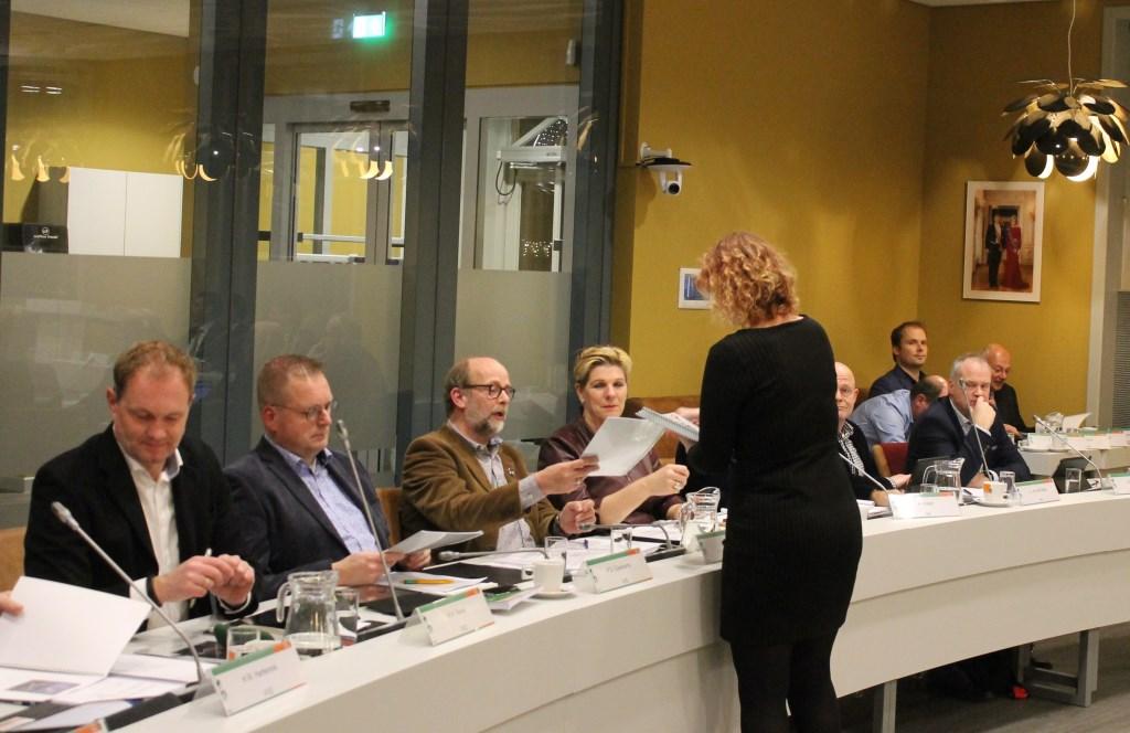 Esther Diepenbroek (Progressieve Partij) deelt de rapporten met de visie uit aan raadsleden en wethouders.  Foto: Leo van der Linde © Persgroep