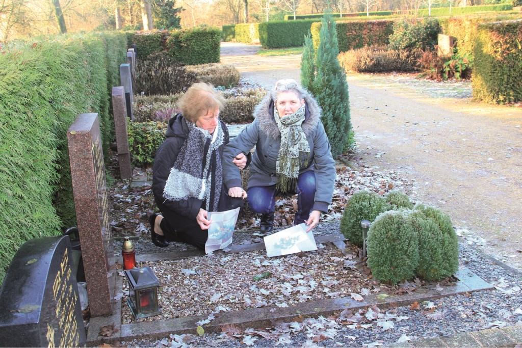 Marian Stienezen (rechts) en Dollie Willemsen bij een van de graven. In hun handen hebben ze foto's van de verdwenen kerststukken.