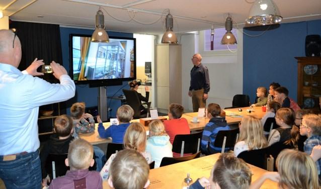 Johan Nijzink van het Rijssens Museum legt de leerlingen van de Holtense Haarschool uit hoe de VR-tour werkt. Foto: Rijssens Museum