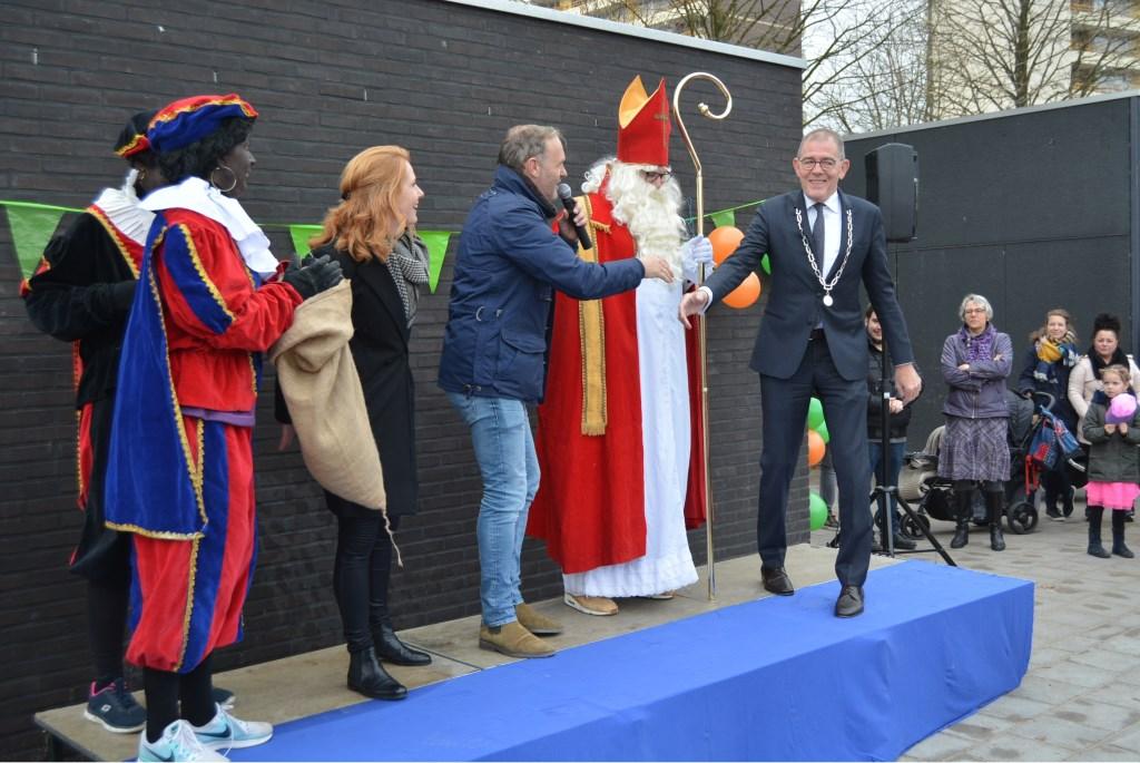 Burgemeester Piet Zoon wordt op het podium gehaald om samen met de Sint het plein te openen.  © Persgroep