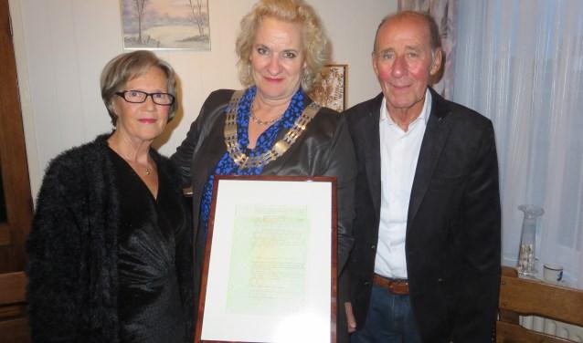 Wim en Marijke samen met loco-burgemeester Wil Kosterman met de gewaarmerkte kopie van de oorspronkelijke trouwakte. FOTO: John Beringen
