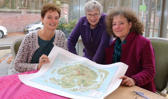 Gerdi Keeler, Gonnie Vijfvinkel en Jetta van Genuchten met de landkaart van 'Het Bekende Land: wat je ziet ben je zelf!'. FOTO: Hanny van Eerden
