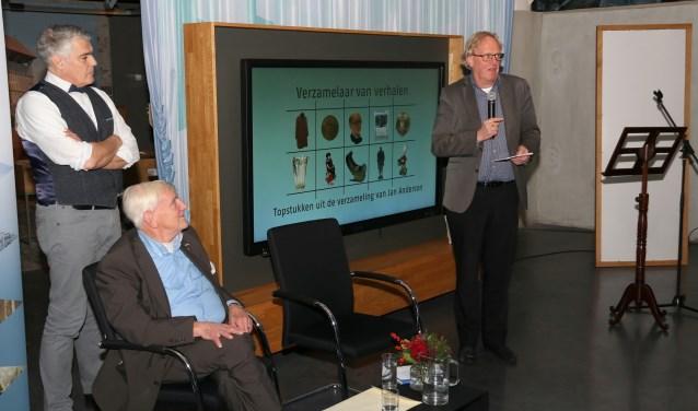 Bart de Leede (rechts) houdt een toespraak tijdens de opening van de tentoonstelling van spullen van Jan Anderson (zittend).