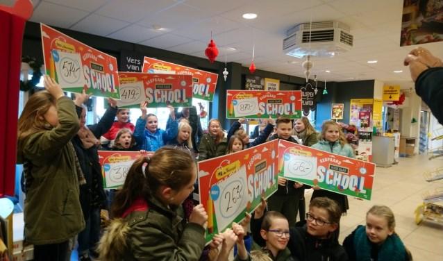 Enthousiast houden de kinderen de cheque in de lucht die hun basisschool heeft gekregen van Jumbo Kalkman.