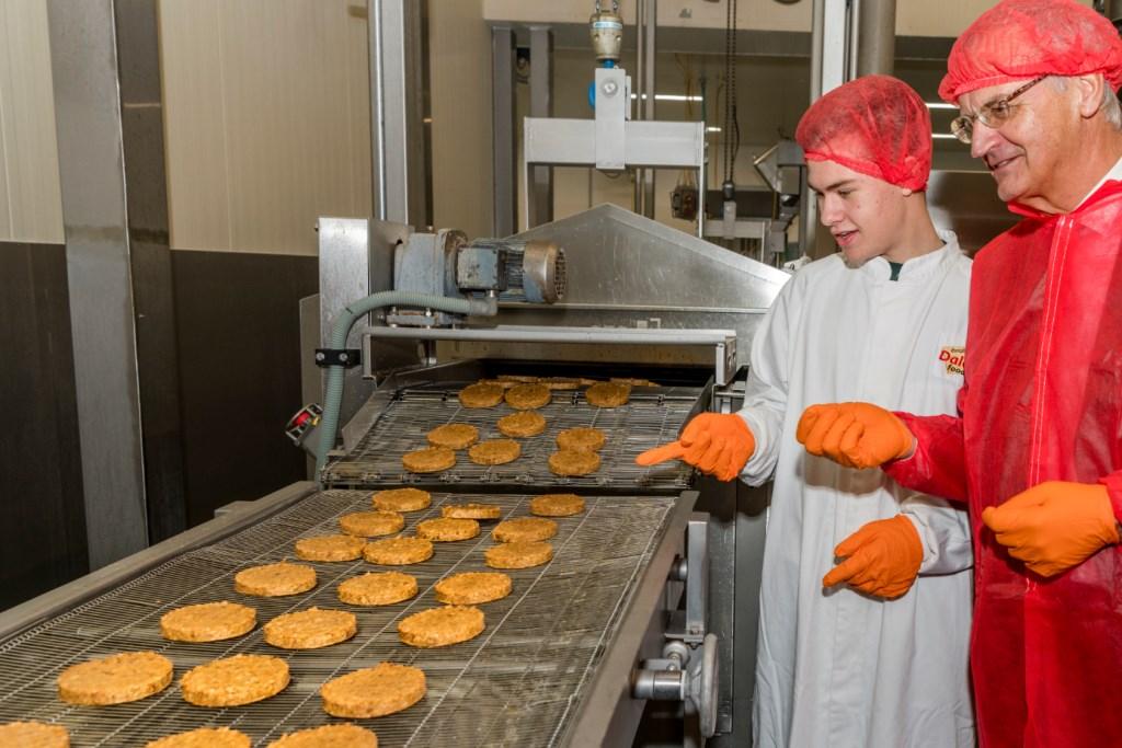 """Stijn Scholten en Europarlementariër Lambert van Nistelrooij zien hoe de eerste wereldburgers bij Dalco Foods van de lopende band rollen. """"Een doorbraak"""", noemt de EU-politicus het.   © Persgroep"""