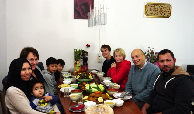 De tafel staat gedekt met mooi opgemaakte Syrische gerechten. Ook de kinderen genieten volop van het heerlijke eten. FOTO: Ellis Plokker