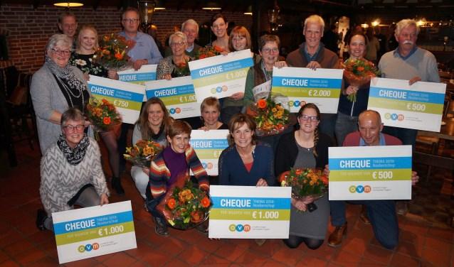 Vertegenwoordigers van de winnende projecten met de cheque en een bos bloemen.