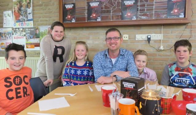 Schooldirecteur Christiaan de Jong zit met enkele kinderen (vlnr Miron, Mara, Amy, Niels en Jasper) klaar voor de high tea-kerstactie van de  Juliana. Op 20 december neemt hij na 18 jaar afscheid van 'zijn' school.