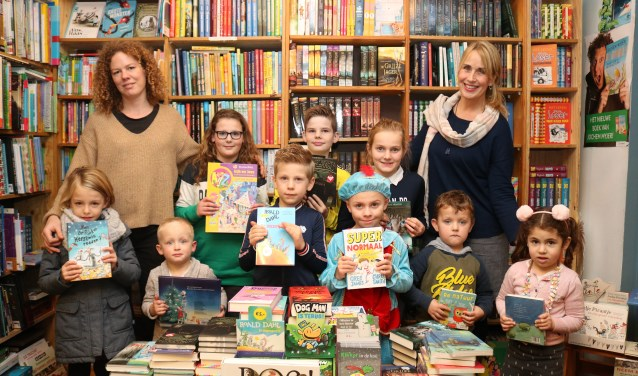 Frederike Scholing (Boekhandel Lovink en (pre)logopediste Irma Wopereis (rechts) met negen van de tien prijswinnaars. (Foto: Arjen Dieperink)