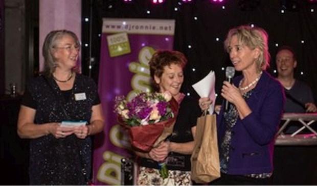 Jackie Kersten van Natuurtuin Bottendaal krijgt symbolisch het 'Lokaal Compliment' uitgereikt door wethouder Visser (rechts) en Mirjam Kaptein (links). (Foto Hans de Groot)