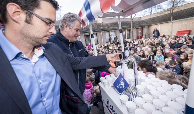 Wethouders Thijs van Kessel (L) tapt de eerste bidon water en proost daarna met Huub Hamers van de Nicolaasschool. Foto: Thomas Segers