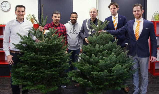 Woerdenaren Eyad en Matiwos ontvingen de eerste kerstbomen uit handen van de burgemeester. FOTO: Alex de Kuijper