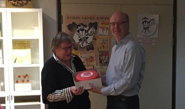 """Fractievoorzitter overhandigt een rode taart aan de vrijwilligers van de """"StOK""""."""
