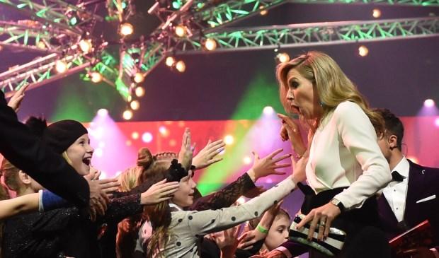 Koningin Máxima deelt 'high fives' uit aan de kinderen in de zaal.