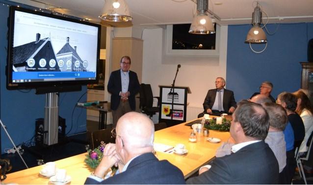 Jannes van de Willige geeft bij het scherm uitleg over Erfgoed Rijssen-Holten. Voorzitter Jan Beumer zit tegen wand. Foto: Jan Joost.