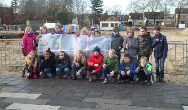 Leerlingen uit groep 5/6 van de Jac. P. Thijsseschool staan met hun banner bij de plek waar hun nieuwe school verrijst. (foto: Marnix ten Brinke)