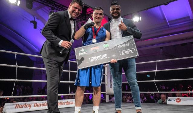 Tijdens Gladiatoren aan de Maas overhandigde GLORY-kickbokser Luis Tavares namens de stichting een cheque aan Artjom Kasparian voor de Stichting Rotterdam Boxing. Links presentator Ray Martin. (Foto: Ellen de Monchy)