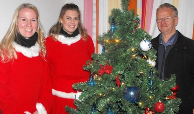 Marjantine Eindhoven, Nyncke Pieterson en Theo Morsinkhof bij de kerstboom in een woonkamer van de JP van den Bent stichting,