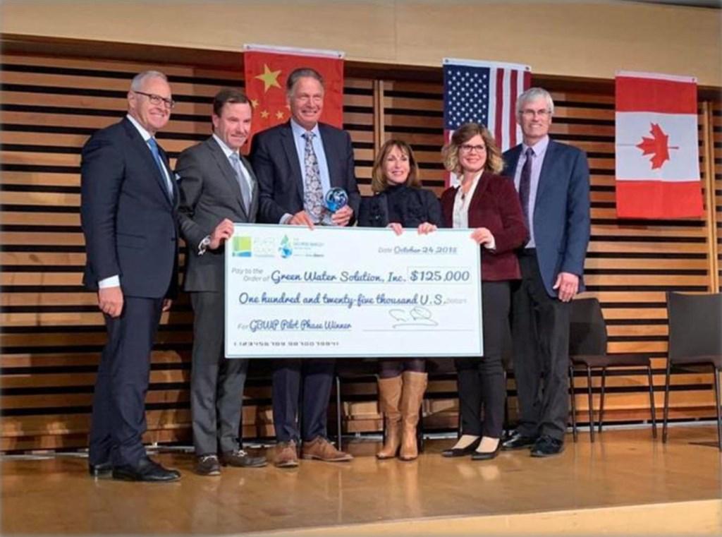 Koos Baas (in het midden) neemt de cheque in ontvangst die hoort bij het bereiken van de finaleplaats in de George Barley Water Prize.  © Persgroep