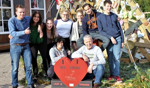 Luuk Broos (zittend rechts),medewerkers en jongeren maken hartjes en roepen iedereen op hetzelfde te doen voor Stichting Hartenkind. Foto: Wendy van Lijssel