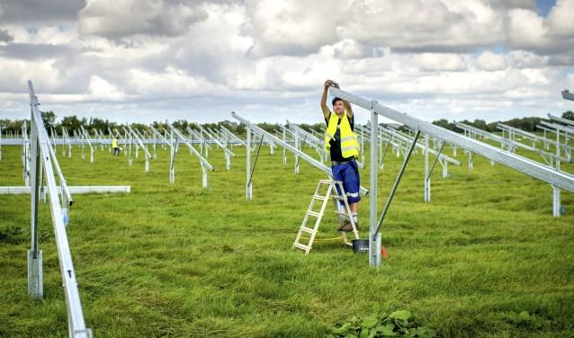 Installateurs zijn bezig met het aanleggen van zonnepanelen. Er zijn plannen voor velden vol zonnepanelen langs de A1. (Foto: Jilmer Postma)