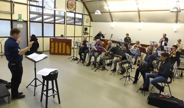 Dirigent Dick Verhoef staat swingend voor de groep muzikanten. Op de foto missen de trompettisten Bram en Bas, die op pad waren met de Pietenband. Foto: Marianka Peters