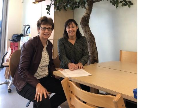 Hetty van de Weg, de Bibliotheek Noord-Veluwe en Jacinta Kiffen, Stichting KOM, tekenen de overeenkomst Boekstart in de Kinderopvang.
