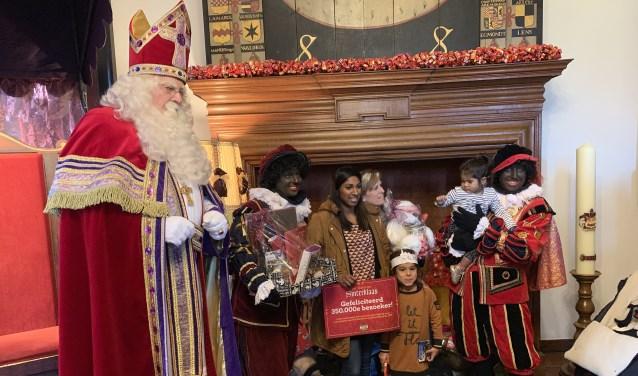 De gelukkige winnaars. Vlnr: Sinterklaas, CadeauPiet, moeder Callista, zusjes Charlie en Nikki, en WegwijsPiet.