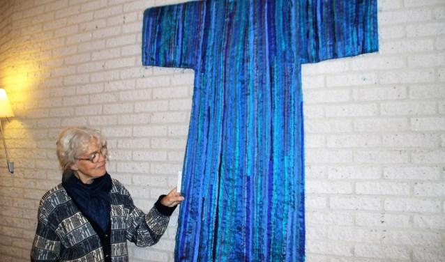 Marijke Jager Burggraaff toont het label waarop staat wat het wandkleed voorstelt. Foto Dick Baas