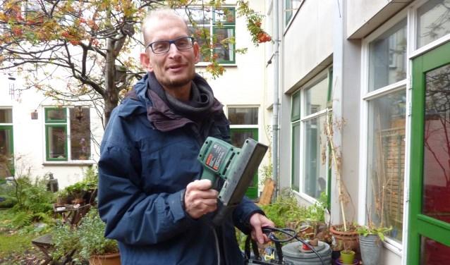 Jeroen, gewapend met schuurmachine en bouwlamp, die straks te lenen zijn bij de 'bibliotheek' voor gereedschappen