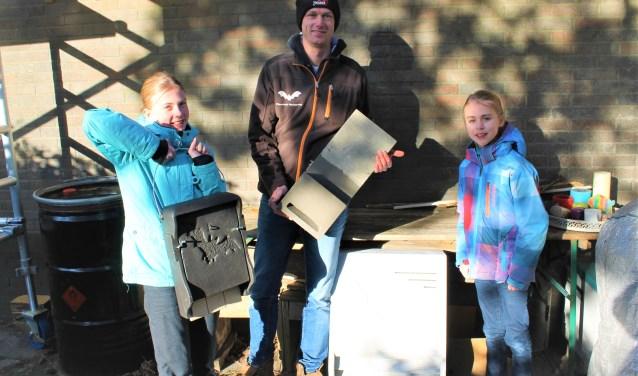 Willem Berger (midden) laat samen met de dochters van de bewoners de verschillende vleermuiskasten zien. De grote lichtgrijze kast op de grond werd even later aan de muur gehangen. (Foto: Leusden Nu)