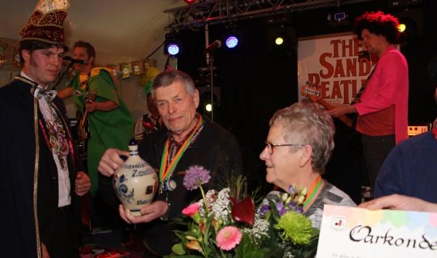 Fons Taken krijgt het Kruukske van Verdienste uit handen van vicepresident Bas Stoltenborg van de Zandbieters, in het bijzijn van zijn vrouw Willy en familie.