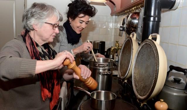 Liesbeth Indemans (l) en Louise Engbers bij het fornuis waar een groot deel van de maaltijd zal worden gekookt.    (foto: Cees Hoogteyling)