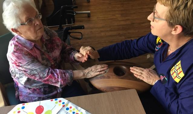 Een bewoonster van BrabantZorg locatie 'de Ruwaard' is met bewegingsbegeleider Hannie Megens (r) in de weer met de CRDL. Ze ziet hoe de CRDL rustgevend kan werken bij dementerende ouderen.