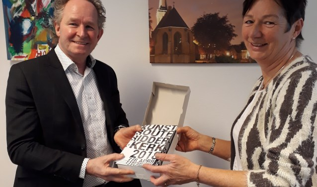 De wethouder Japenga kreeg als eerste het feestelijke boekje van de Kunstroute Ridderkerk aangeboden door Erna Wouters.