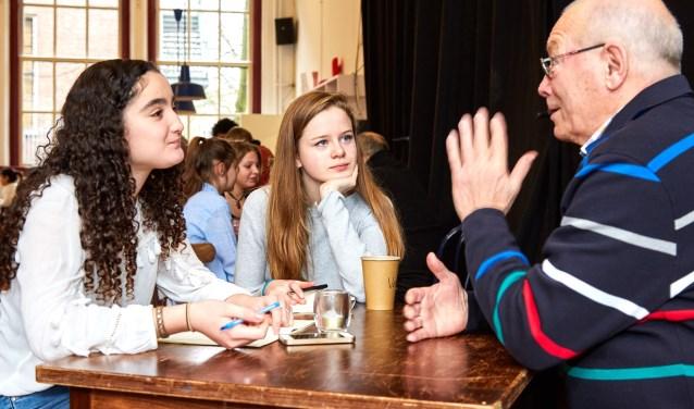 Jongeren luisteren aandachtig naar de verhalen van ouderen. Met deze verslagen gaan ze zelf een voorstelling bedenken en maken.(Foto: Studio Johan Nieuwenhuize)
