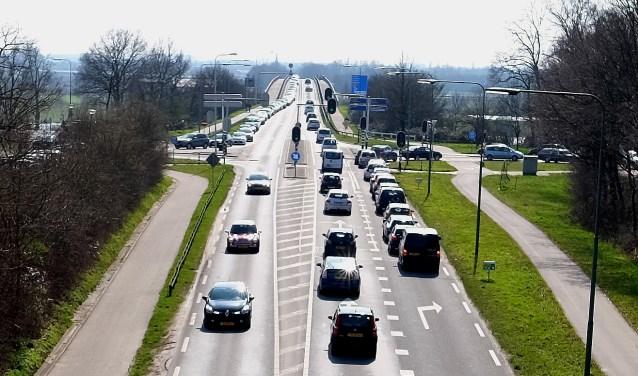 De Rijnbrug bij Rhenen staat regelmatig vast in de spits. In het midden de kruising, waar stoplichten volgens kenners het fileleed verergeren. (foto Max Timons)