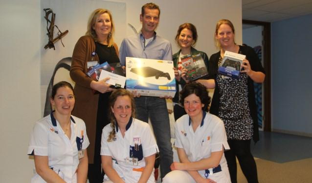 V.l.n.r. staand: Esther van Wanrooy (unitleider kinderafdeling), Leon en Wendy Roelofs en Sanne de Leeuw (pedagogisch medewerker). Op de voorgrond gehurkt drie verpleegkundigen