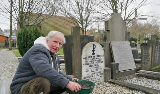 """Walter van der Corput aan het werk op de RK begraafplaats op het Emaus. """"De steen weer recht te zetten, alles goed schoon te maken en de tekst weer zichtbaar te maken"""", legt hij uit (Foto: Peter Spek)."""