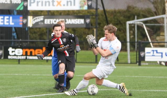 VIOD speler Lukas de Graaf in kansrijke positie om een doelpunt te scoren. PAX doelman Jeroen van der Veen weet de bal te stoppen.