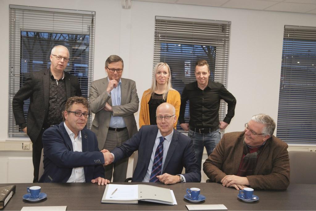 Ferdinand van den Oord (links) en burgemeester Arend van Hout schudden elkaar de hand na het ondertekenen van de overeenkomst. Staand vlnr: Martin Wieleman, Kees Krechting, Debbie Veldink en Arjan Hetterscheit. Rechts zit wethouder Hans Sluiter.