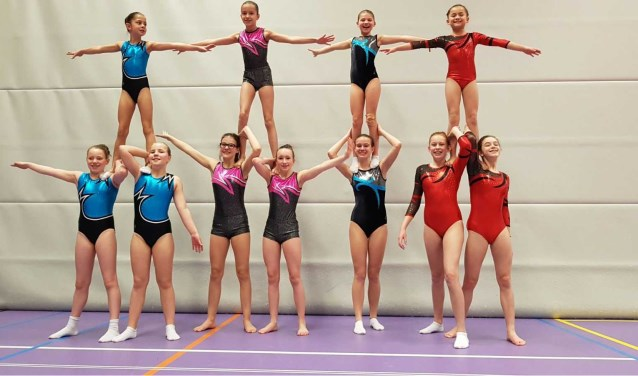 De acrogymnasten op een rij.