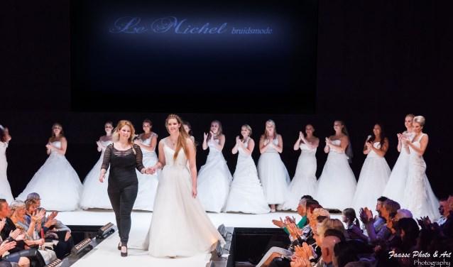 """Michelle Schuurmans (27) loopt met een bruidsmodel over de catwalk tijdens een modeshow bij Theater aan de Parade in Den Bosch. """"Dit werk is echt mijn passie. Ik word er elke keer weer zo vrolijk van."""""""