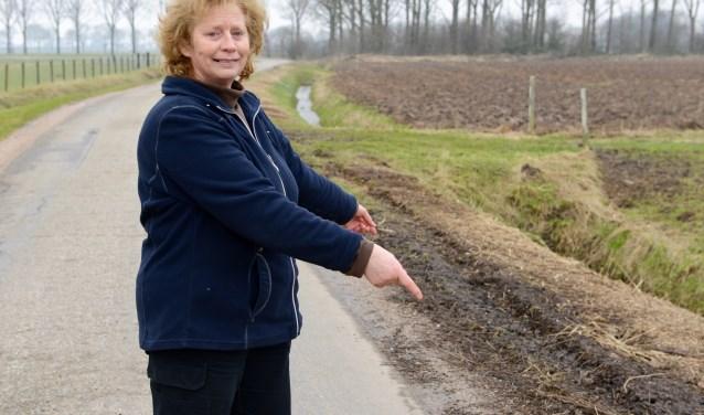 Mevrouw Wanda de Vos toont de slechte berm aan de Veldweg, vaak veroorzaakt door zwaar landbouwverkeer. Voor de gemeente is de Veldweg nog niet aan de beurt.   (foto's: Cees Hoogteyling)