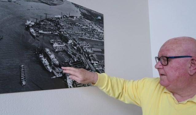 Peter Groenendijk wijst in de hal van het appartementengebouw waar hij woont, de plek aan op een historische foto van de Boele werf. (foto GvS)