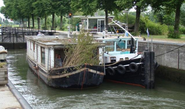 De Christina, dit nog als woonboot opgebouwde schip ligt voor de kade in het water.