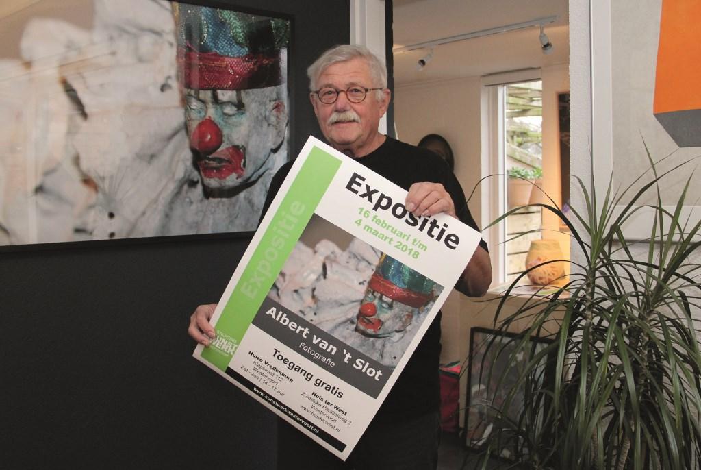 Albert van 't Slot met het affiche dat zijn foto-expositie in Huize Vredenburg en Huis ter West aankondigt.