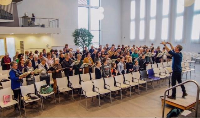 Op de voorgrond Niels Kuijers, dirigent; daarachter het kinderkoor, Laudate, Cantate en Hans Houtman, organist. (Foto: Privé)